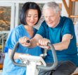 caregiver and elder man having physical therapy