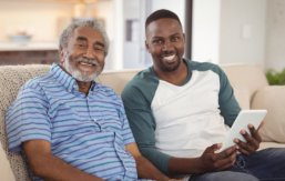 caregiver and elder man smiling