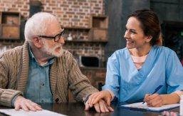 caregiver and elder man holding hands