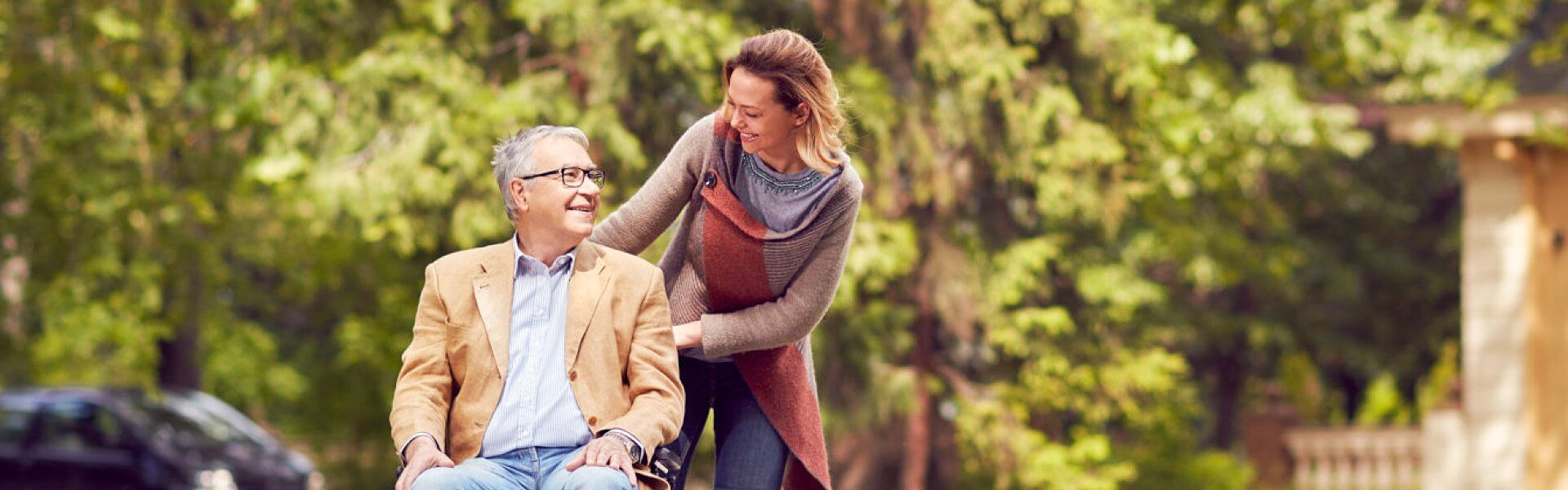 caregiver and elder man smiling at each other