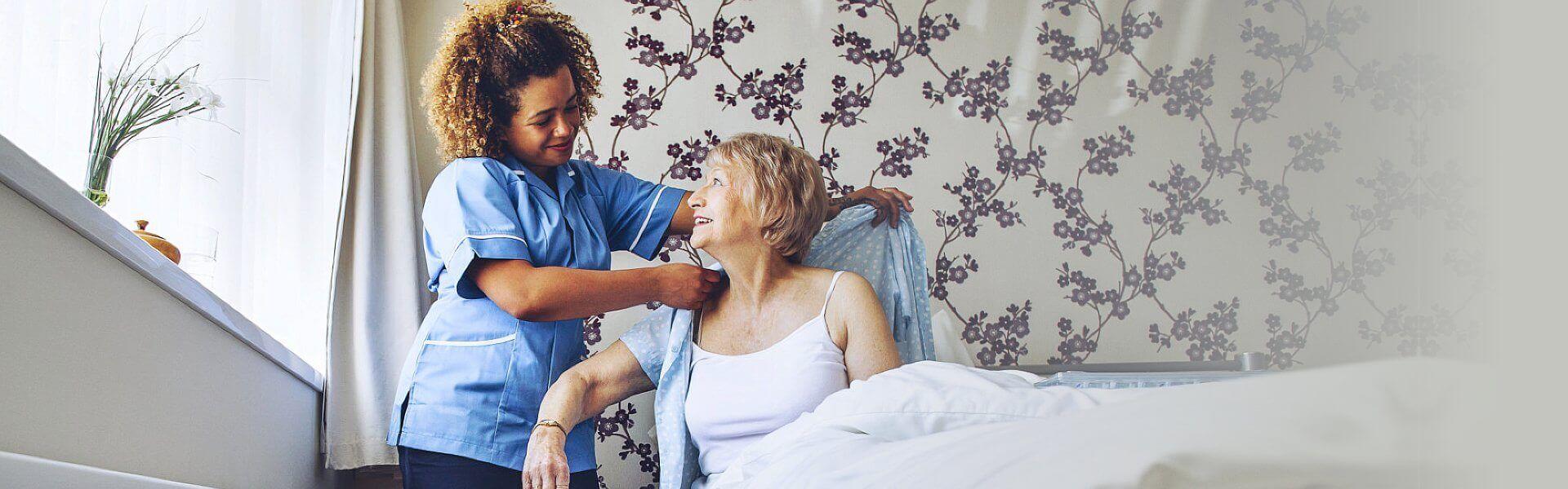 caregiver helping elder woman get dressed