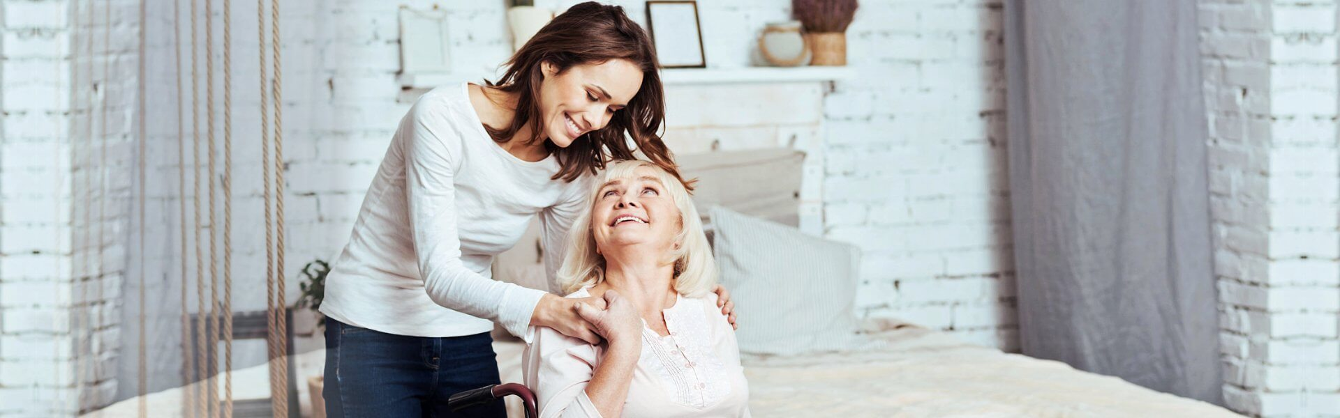 caregiver and elder woman smiling at each other
