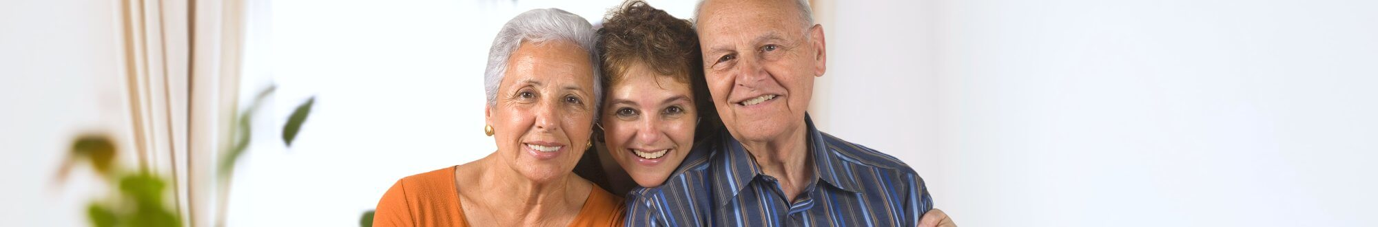 caregiver and an elderly couple smiling