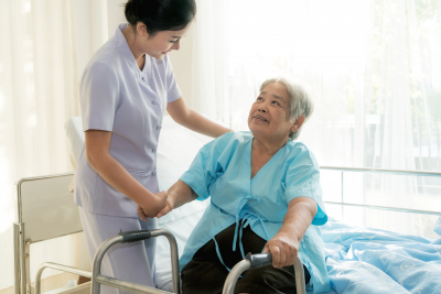 Asian young nurse supporting elderly patient disabled woman