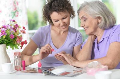 Nurse polishing the nail of an elder woman