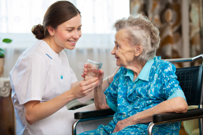 Caregiver helping an elderly woman drinking water