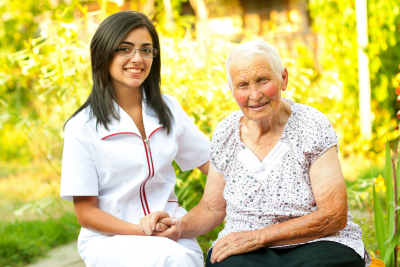 Caregiver and an elderly woman smiling