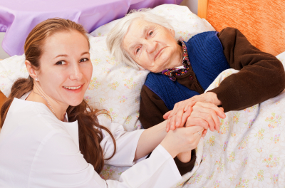 Young caregiver holds the old woman's hands