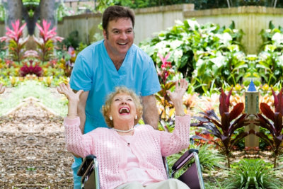 Caregiver pushing an elderly woman in a wheelchair